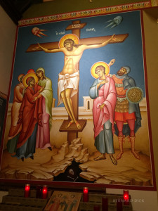 A very large crucifixion icon is to the left of the iconstasis screen.